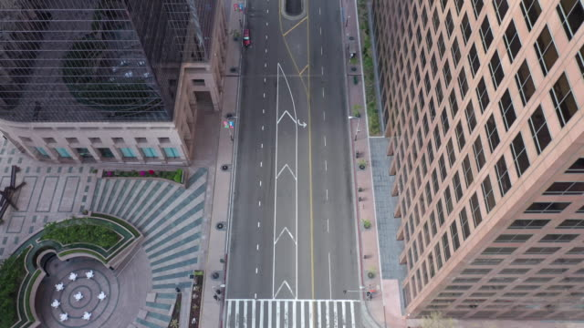 flying over empty downtown street during coronavirus pandemic - edificio adibito a uffici video stock e b–roll