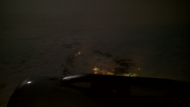 Flying Over Europe at Night, Looking at City Lights through Porthole
