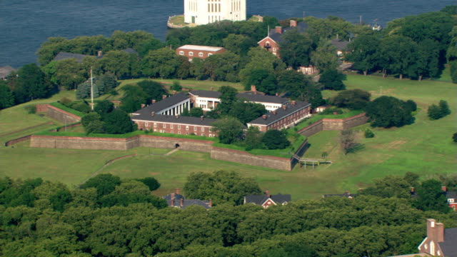 flying over governors island with view of manhattan. shot in 2003. - fortezza video stock e b–roll