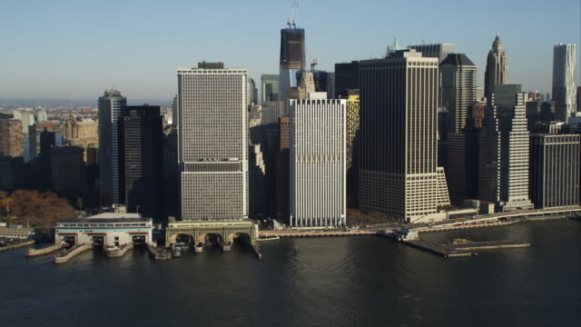 Flying over harbor toward Financial District in Lower Manhattan, ferry terminal on waterfront at left. Shot in 2011.
