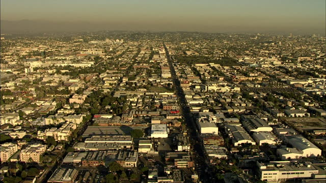 Flying over Hollywood city various urban low midrise buildings traffic on streets below LA CA