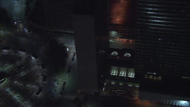 Flying over lighted downtown Dallas park Sheraton hotel highrise office buildings Trammell Crow Center Bank of America Tower Reunion Observation...