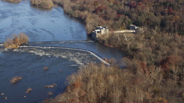 vídeos de stock, filmes e b-roll de flying over little falls dam and pumping station on the potomac river in autumn, maryland shoreline at right. shot in november 2011. - artbeats