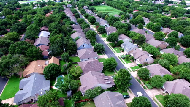 aerial: flying over local austin texas housing complex with natural trees and texas hill country feel backing up - home ownership stock videos & royalty-free footage