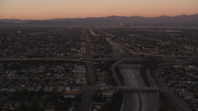 vídeos de stock e filmes b-roll de flying over los angeles freeways and interchanges toward downtown in evening light. shot in 2010. - trevo de quatro folhas