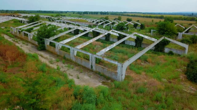 flying over old abandoned architectural construction at dry field - abbandonato video stock e b–roll