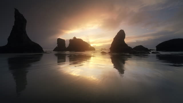 vídeos de stock, filmes e b-roll de flying over pacific beach at low tide, bandon, oregon - vazante
