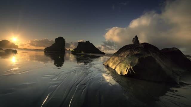 vídeos de stock, filmes e b-roll de flying over pacific beach at low tide, bandon, oregon - coluna de calcário marítimo
