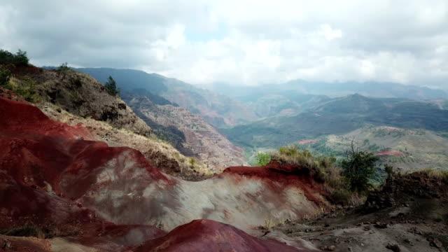 vídeos de stock, filmes e b-roll de voando sobre rochas vermelhas em direção a enorme vale abaixo na ilha - overcast