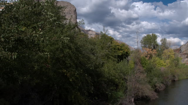 vidéos et rushes de flying over river and trees towards rocky cliff face - provo