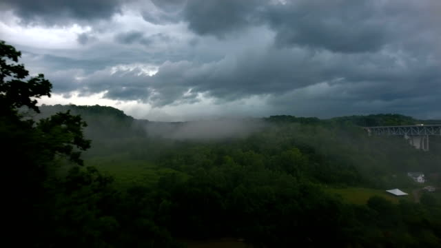 vídeos de stock e filmes b-roll de flying over river valley in thunderstorm - nublado