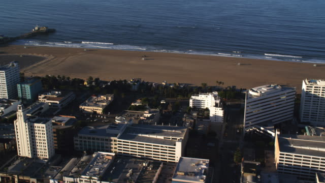 flying over santa monica beachfront hotels toward santa monica pier. shot in 2010. - santa monica pier stock videos & royalty-free footage