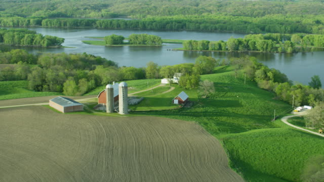 flying over shot of a farm by the mississippi river - riverbank stock videos & royalty-free footage