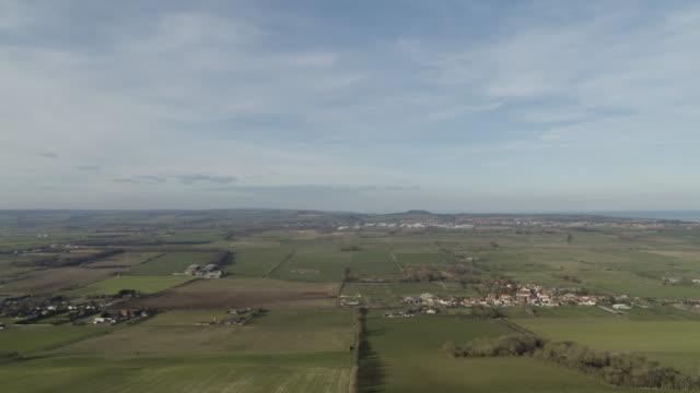 flying over shot of the hilly meadows near flixton - 英国スカーブラ点の映像素材/bロール