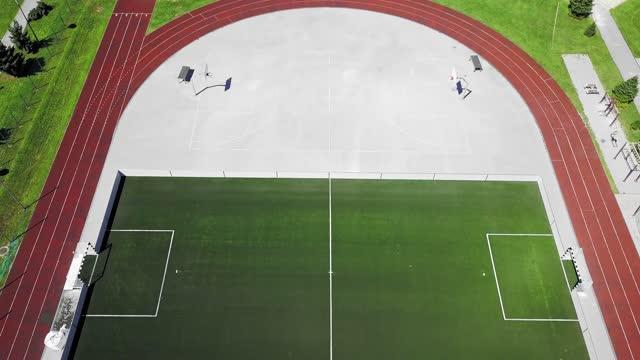 人がいないスポーツスタジアムの上空を飛ぶ - 球技場点の映像素材/bロール
