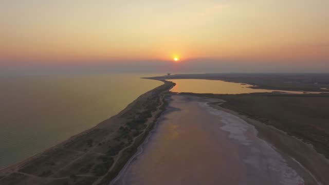 vídeos de stock, filmes e b-roll de voando sobre a superfície dos lagos salgados no pôr do sol, aerial video - remanso