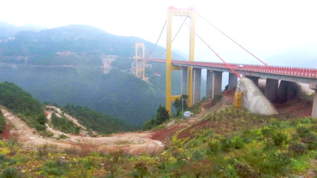 flying over suspension bridge connect between the mountain with drone, ghuizhou, china - high up stock videos & royalty-free footage