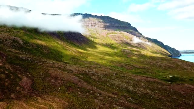 flying over the clouds in iceland along the coast - natural landmark stock videos & royalty-free footage