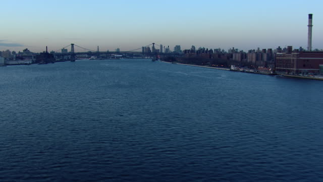 flying over the east river towards the williamsburg bridge in new york city. - williamsburg bridge stock videos and b-roll footage