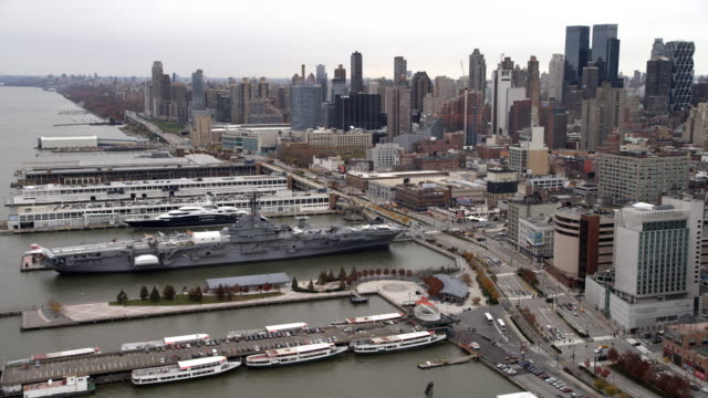 Flying over the Hudson past Midtown Manhattan, naval carrier USS Intrepid at dock. Shot in 2011.