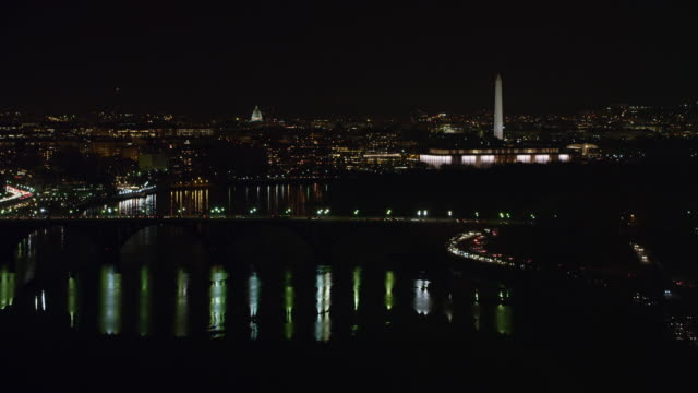 stockvideo's en b-roll-footage met flying over the potomac toward key bridge at night, washington dc cityscape beyond with washington memorial parkway traffic at right. shot in 2011. - john f. kennedy