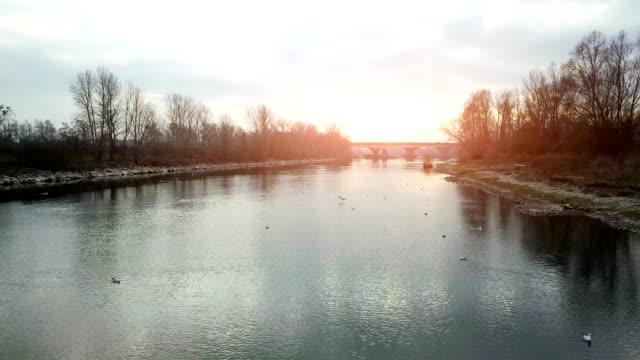 Fliegen über den Fluss bei Sonnenuntergang