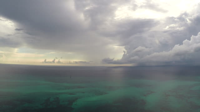 Flying over the tropical Blue Turquoise waters of North Key Largo FL A severe thunderstorms ominous clouds loom on the horizon