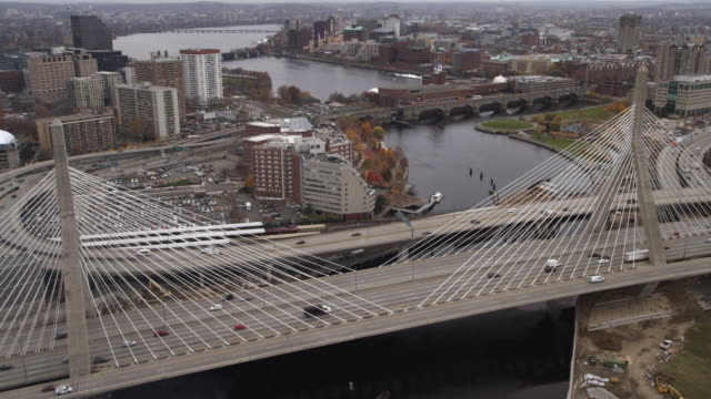 flying over the zakim bunker hill bridge on the charles river in boston toward a commuter train viaduct with longfellow and harvard bridges in distance. shot in 2011. - charles bridge stock-videos und b-roll-filmmaterial