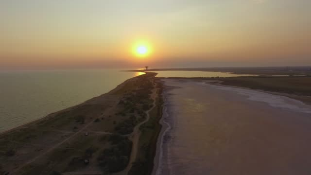 flying over touristic area between blue sea and salt lakes on sunset, aerial video - backwater stock videos & royalty-free footage