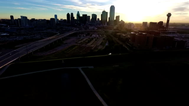 AERIAL: Flying over Trinity River Dallas Texas Epic Sunrise Downtown Skyline with Reunion Tower turning to see city