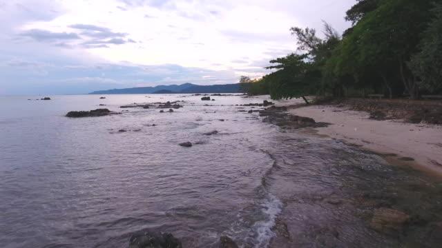 flying over tropischen meer und rocky beach in der abenddämmerung, aerial video - klammer stock-videos und b-roll-filmmaterial