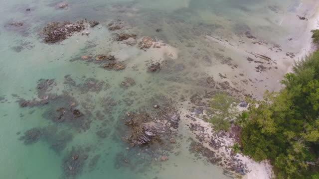 vidéos et rushes de flying over tropical mer et rocky beach avec de l'eau cristalline, vidéo aérienne - pince à papier
