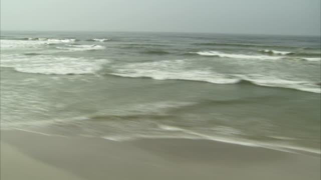 flying over waves washing onto a sandy beach. - küste stock-videos und b-roll-filmmaterial