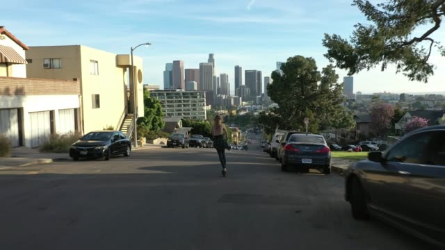 flying over young woman riding scooter down street revealing downtown los angeles - motorino video stock e b–roll