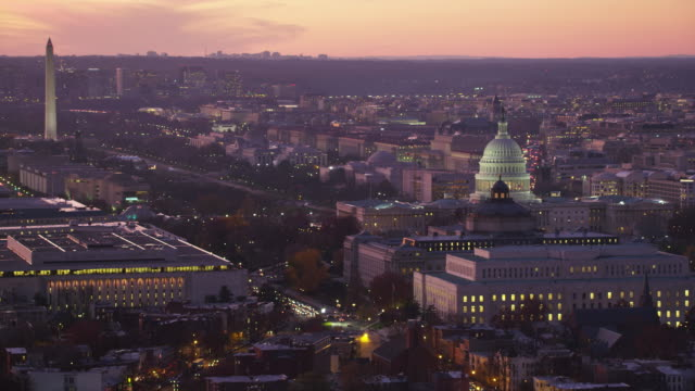 Flying past Capitol Hill and Library of Congress  at dusk, crossing Pennsylvania Avenue with Mall and city in background, National Cathedral on skyline. Shot in 2011.
