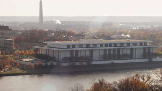 flying past kennedy center on a hazy day  in washington dc. washington monument in rear. shot in 2011. - john f. kennedy center for the performing arts stock videos & royalty-free footage