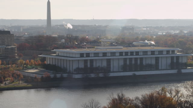 flying past kennedy center on a hazy day in washington dc; washington monument in rear. shot in 2011. - john f. kennedy center for the performing arts stock videos and b-roll footage