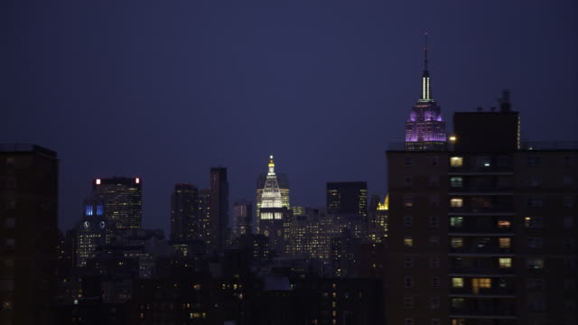 flying past midtown manhattan skyline at night, empire state building at right. shot in 2011. - artbeats stock-videos und b-roll-filmmaterial