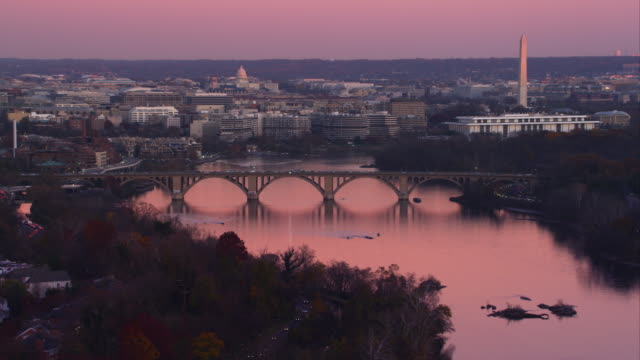 Flying past the Key Bridge over the Potomac River at dusk in Washington DC; left to right behind bridge are Georgetown University, Watergate Complex, the Kennedy Center, and Washington Monument with the Capitol in rear mid-frame. Shot in 2011.
