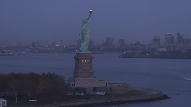 flying past the statue of liberty at dusk; manhattan skyline on right, jersey city at left. shot in 2011. - artbeats stock videos & royalty-free footage