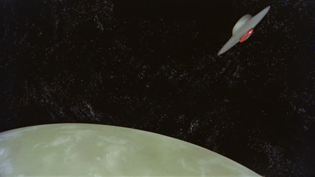vidéos et rushes de flying saucer flying above planet surface away from camera in space / forbidden planet (1956) - ovni