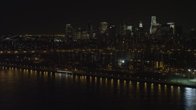 flying south along the east river toward williamsburg bridge at night, new york financial district in background. shot in 2011. - williamsburg bridge stock videos & royalty-free footage