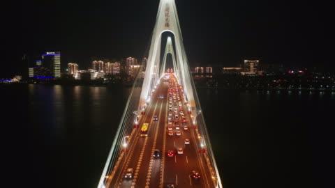 flying through centry bridge while serious traffic jam, haikou city hainan province - hängbro bildbanksvideor och videomaterial från bakom kulisserna