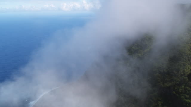 Flying through mist along Molokai's coastal cliffs
