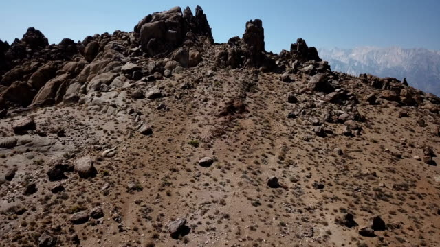flying through rocks reveal distant snowcapped mountains - desert oasis stock videos & royalty-free footage