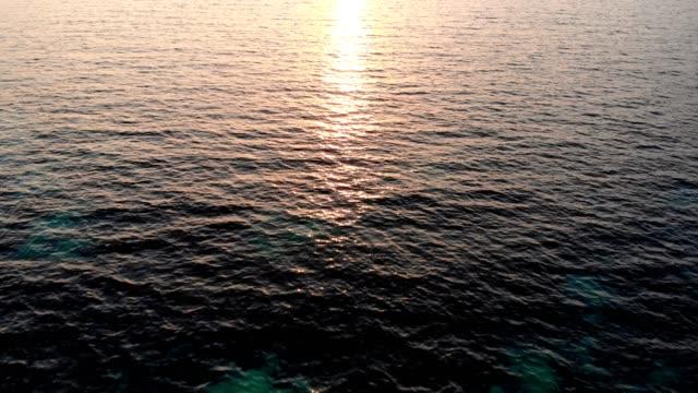 vidéos et rushes de vol au coucher du soleil avec croisière de yacht en mer tropicale - horizon over water