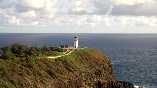 flying toward lighthouse perched on egde of kauai island - butte rocky outcrop stock videos & royalty-free footage