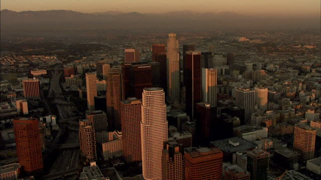 Flying toward over downtown LA skyline of highrise buildings skyscrapers including US Bank tower CA Central business district financial district