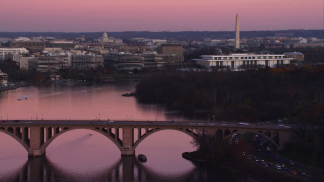 Flying toward the Key Bridge over the Potomac River at dusk in Washington DC; left to right behind bridge are Georgetown University, Watergate Complex, the Kennedy Center, and Washington Monument with the Capitol in rear mid-frame. Shot in 2011.