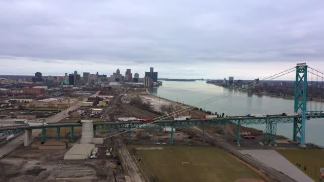 flying towards downtown detroit over the ambassador bridge - detroit river stock-videos und b-roll-filmmaterial